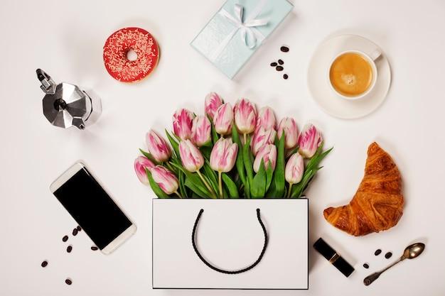 Bovenaanzicht van lentebloemen, koffie, mobiele telefoon, croissants