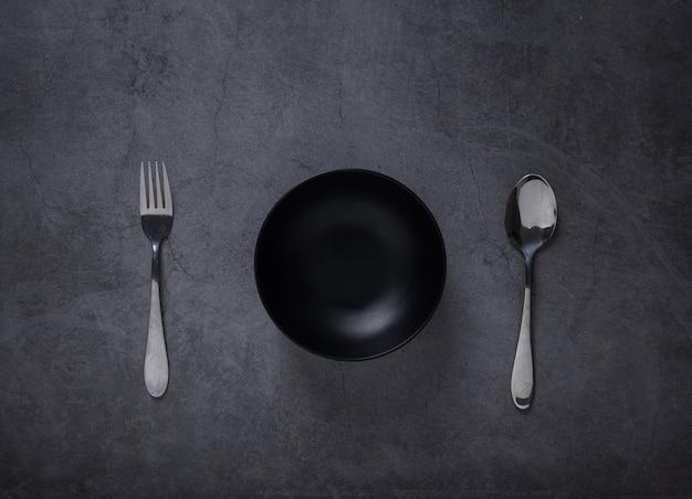 Bovenaanzicht van lepel en lege kom op donkere cement tafel