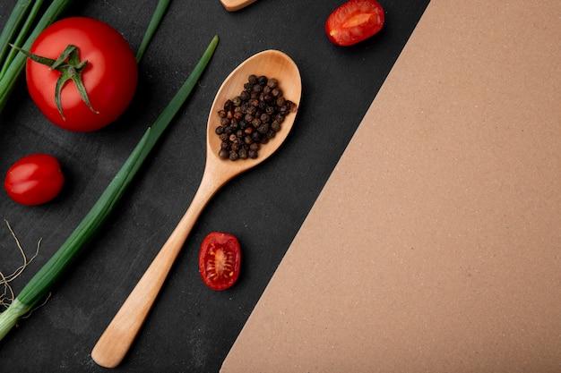 Bovenaanzicht van lepel vol peper kruiden met tomaten en lente-uitjes op zwart oppervlak met kopie ruimte