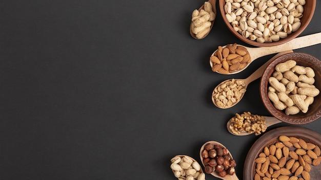 Bovenaanzicht van lepels en kom met assortiment van noten en kopie ruimte