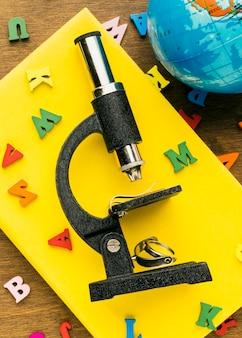 Bovenaanzicht van letters met microscoop en globe