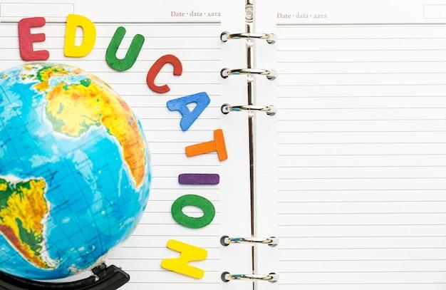 Bovenaanzicht van letters op notebook met globe