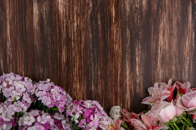 Bovenaanzicht van licht roze bloemen met lelies en rozen op een houten oppervlak
