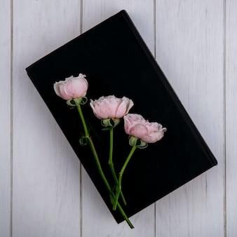 Bovenaanzicht van licht roze rozen op een zwart boek op een grijze ondergrond