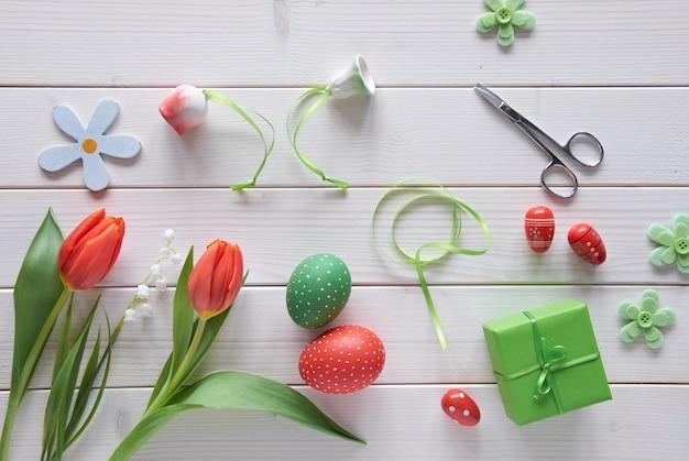Bovenaanzicht van lichte houten tafel met lente decoraties, ingepakt cadeau, vilt bloemen, rode tulpen en en paaseieren