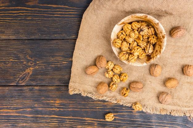 Bovenaanzicht van lichtjes verspreide walnoten liggend op linnen doek in de buurt van houten plaat met walnoten op houten bureau.