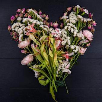 Bovenaanzicht van lichtroze bloemen in de vorm van een hart op een zwarte ondergrond