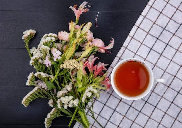 Bovenaanzicht van lichtroze bloemen met een kopje thee op een witte geruite handdoek op een zwarte ondergrond