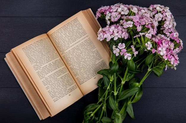 Bovenaanzicht van lichtroze bloemen met een open boek op een zwarte ondergrond