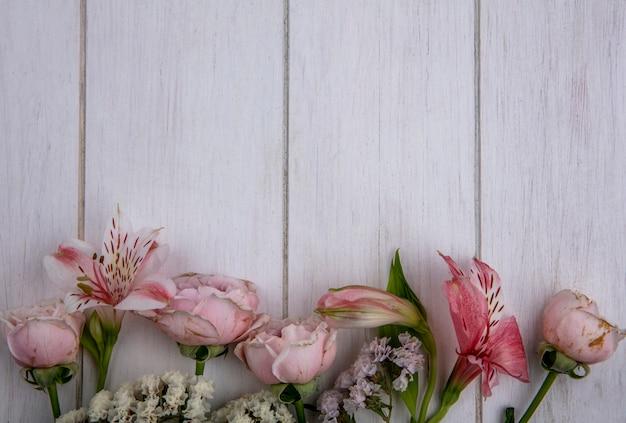 Bovenaanzicht van lichtroze bloemen op een grijze ondergrond