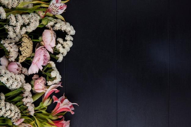 Bovenaanzicht van lichtroze bloemen op een zwarte ondergrond