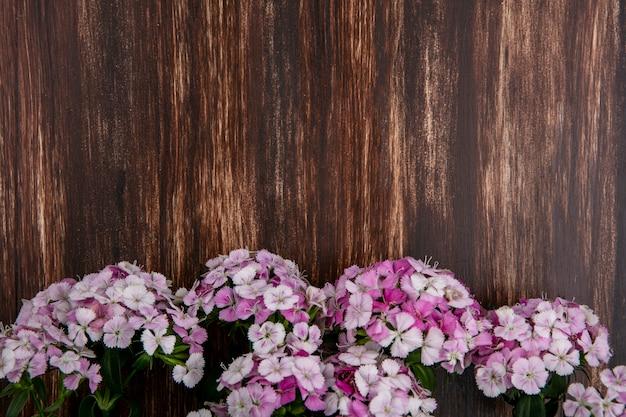 Bovenaanzicht van lichtroze bloemen op houten oppervlak