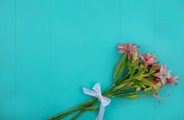 Bovenaanzicht van lichtroze lelies op een lichtblauw oppervlak