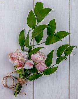 Bovenaanzicht van lichtroze roos met een tak van bladeren en een lelie op een grijze ondergrond