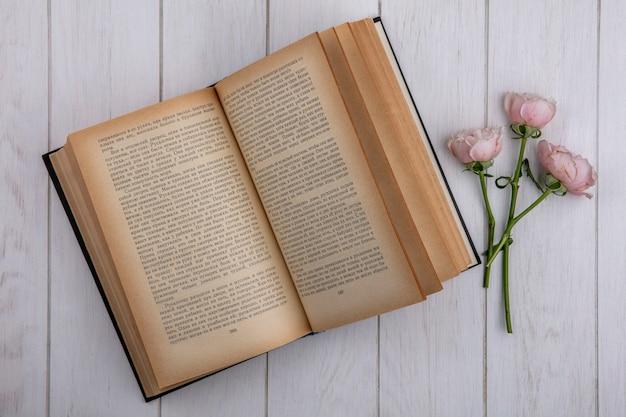 Bovenaanzicht van lichtroze rozen met een open boek op een grijze ondergrond