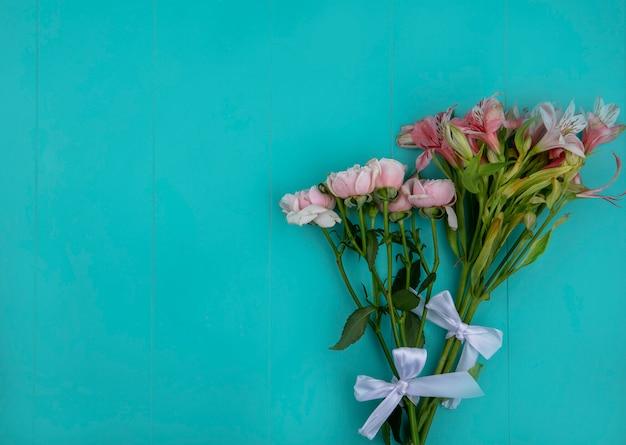 Bovenaanzicht van lichtroze rozen met lelies op een lichtblauw oppervlak