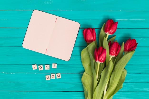 Bovenaanzicht van liefde; moedertekst; lege kaart en rode tulp bloemen over groene houten plank