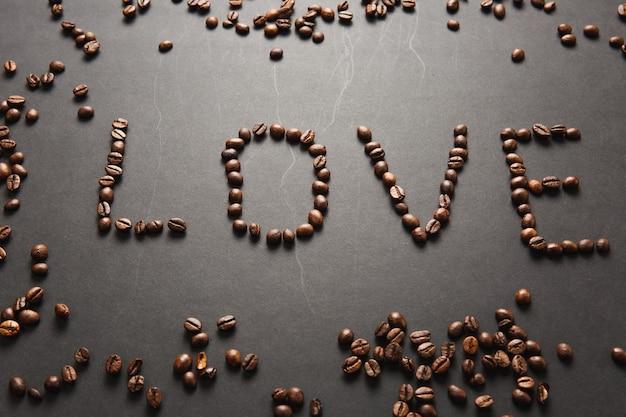 Bovenaanzicht van liefdesbrief, woord gemaakt van koffiebonen op zwarte achtergrond voor design