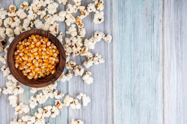 Bovenaanzicht van likdoorns op houten kom met popcorn geïsoleerd op grijs met kopie ruimte