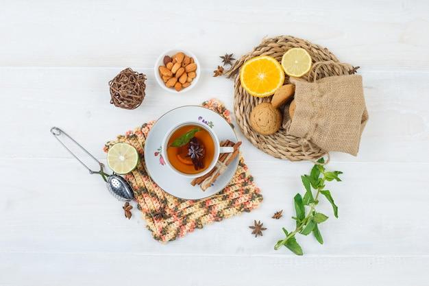 Bovenaanzicht van limoenen en koekjes op ronde placemat met een kopje thee