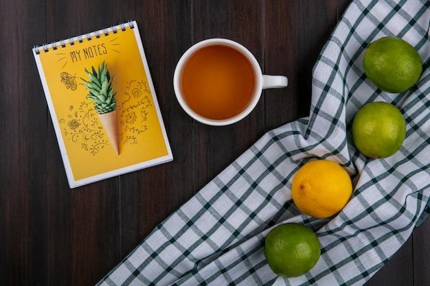 Bovenaanzicht van limoenen (lemmetjes) met citroen op een geruite handdoek met een kopje thee en een notitieblok op een houten oppervlak