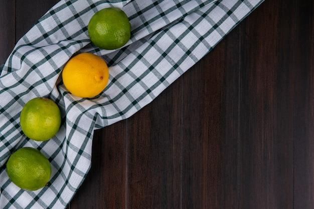 Bovenaanzicht van limoenen (lemmetjes) met citroen op een geruite handdoek op een houten oppervlak