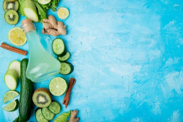 Bovenaanzicht van limoensap met citroen kiwi limoen kaneel gember en anderen aan de linkerkant op blauwe achtergrond met kopie ruimte