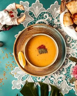 Bovenaanzicht van linzen merci soep in een kom met een schijfje citroen