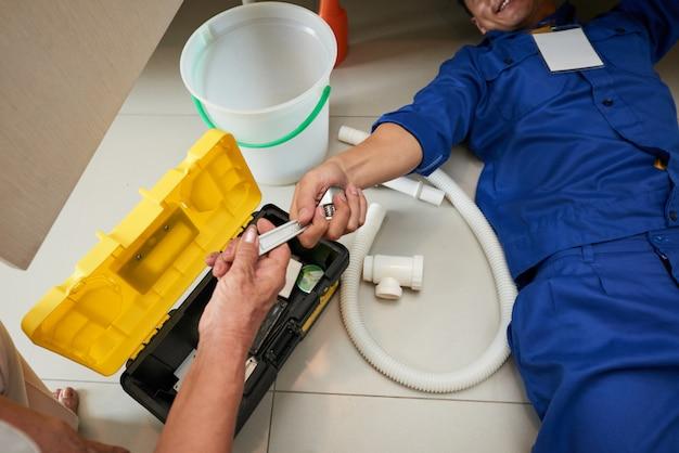 Bovenaanzicht van loodgieter die de keukeninrichtingen controleert