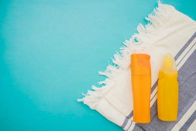 Bovenaanzicht van lotions en handdoek op blauw oppervlak