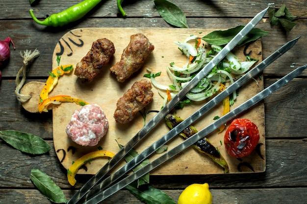 Bovenaanzicht van lula kebab met ui kruiden gegrilde groenten en spiesjes op een houten bord