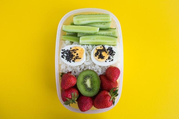 Bovenaanzicht van lunch in de doos op het gele oppervlak