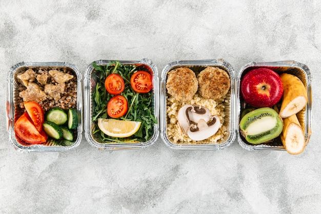 Bovenaanzicht van maaltijden in stoofschotels met groenten en fruit