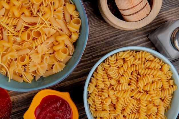 Bovenaanzicht van macaronis als rotini en anderen in kommen met ketchup zout zwarte peper op hout