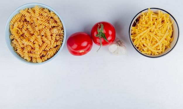 Bovenaanzicht van macaronis als rotini en tagliatelle met tomaten en knoflook op wit met kopie ruimte