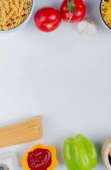 Bovenaanzicht van macaronis als rotini en vermicelli met tomatenketchup knoflook peper zout op wit met kopie ruimte