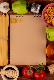 Bovenaanzicht van macaronis als spaghetti en anderen knoflook peper tomaat zwarte peper zout boter rond notitieblok op hout met kopie ruimte