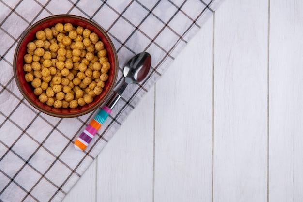 Bovenaanzicht van maïs ballen in een kom met een gekleurde lepel op een geruite handdoek op een wit oppervlak