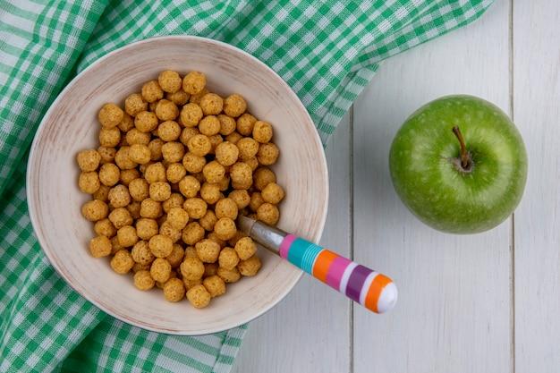 Bovenaanzicht van maïs ballen op een geruite handdoek met een gekleurde lepel en een groene appel op een wit oppervlak