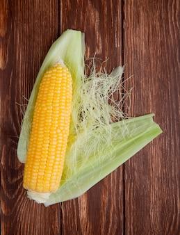 Bovenaanzicht van maïs met schelp op hout