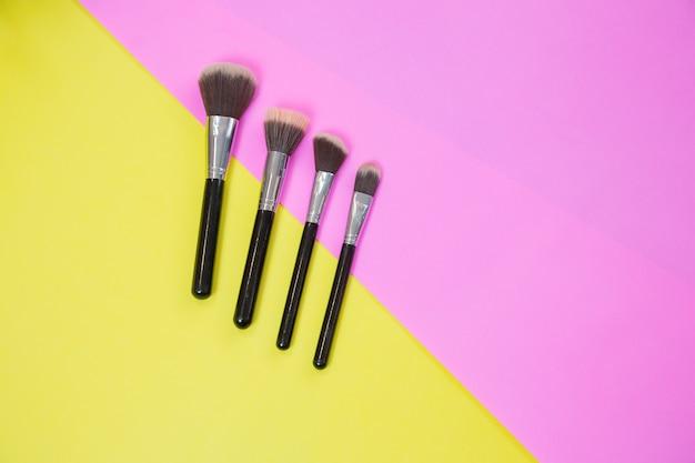 Bovenaanzicht van make-up cosmetica en borstels producten op kleurrijke achtergrond met kopieerruimte