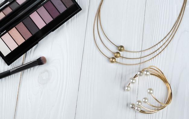 Bovenaanzicht van make-up en gouden ketting en armband met parels accessoires op witte houten oppervlak