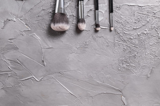 Bovenaanzicht van make-upborstels op grijze achtergrond met copyspace