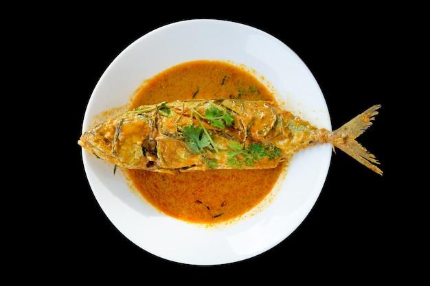 Bovenaanzicht van makreel in gedroogde rode curry op zwart geïsoleerd, focus selectief.