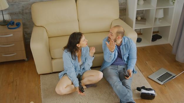 Bovenaanzicht van man en vrouw die vechten tijdens het spelen van videogames op console
