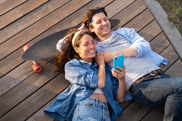 Bovenaanzicht van man en vrouw met skateboard kijken naar video of foto's op smartphone
