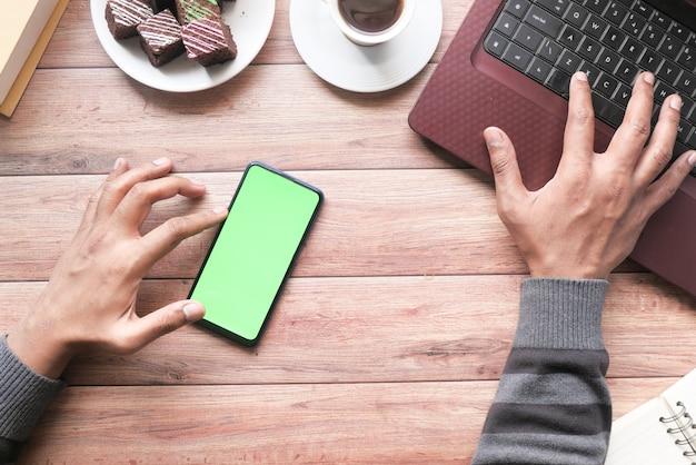 Bovenaanzicht van man hand met behulp van slimme telefoon en typen op laptop