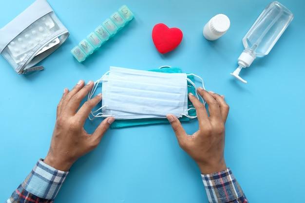 Bovenaanzicht van man hand met chirurgisch gezichtsmasker op blauwe achtergrond Premium Foto