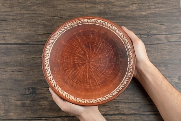 Bovenaanzicht van man hand met een lege bruine plaat op een houten tafel.
