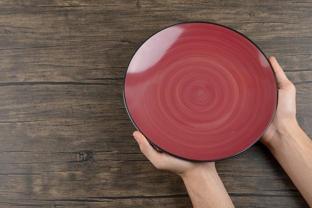 Bovenaanzicht van man handen met een lege rode plaat op een houten tafel.